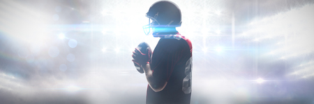 American football player in helmet standing with football against sports pitch