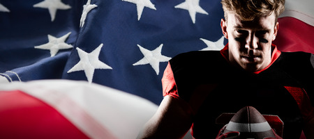 American football player holding rugby ball against full frame of american flag