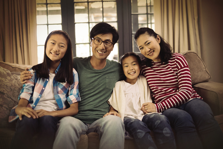 Portrait of smiling family relaxing on sofa in living room at home 写真素材 - 113329550