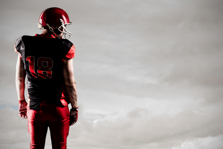 American football player standing in rugby helmet against blue sky with clouds Stock fotó
