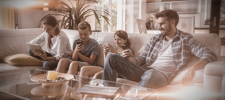 Family using digital tablet and mobile phone in living room at home
