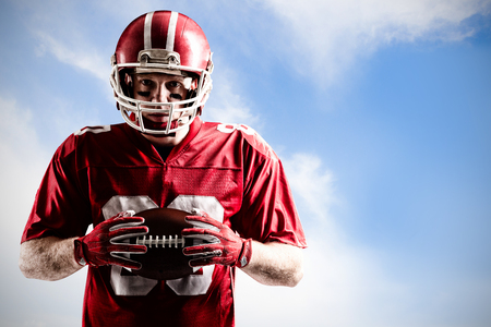 American football player standing with rugby helmet and ball against blue sky with clouds