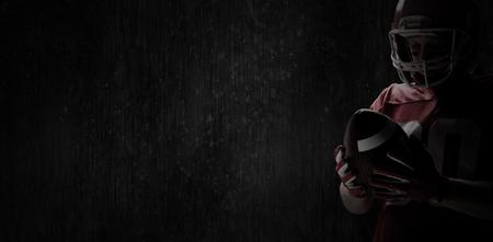 American-Football-Spieler mit Rugby-Helm und Rugby-Ball gegen Full-Frame-Schuss von schwarz gemusterter Wand