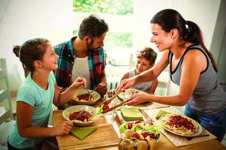 Smiling woman serving meal to family at home