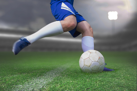 Football player kicking ball against close-up of soccer field