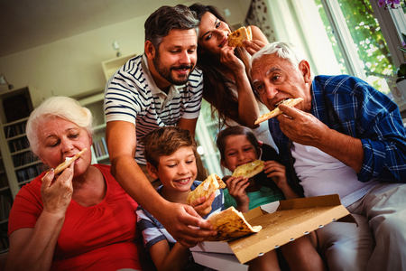 Multi-generation family eating pizza together at home Standard-Bild - 114785159