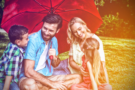Happy family with umbrella sitting on grass at yard Banco de Imagens