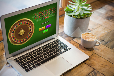 Online Roulette Game  against laptop and potted plant on table Stock Photo
