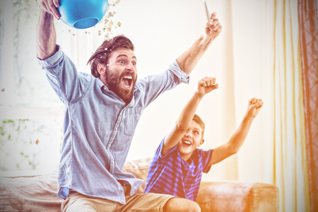 Excited father and son watching television in living room