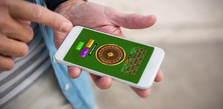 Online Roulette Game  against midsection of man using phone