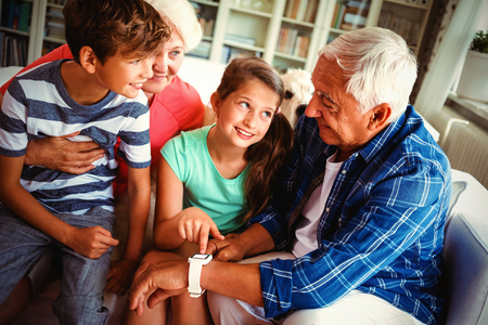 Grandparents and grandchildren looking at smartwatch in living room at home 写真素材