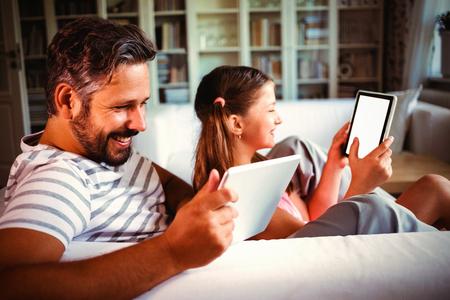 Father and daughter using digital tablet in living  room at home