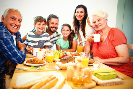 Portrait of happy multi generation family sitting at breakfast table in home