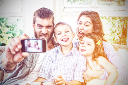 Happy family taking a selfie on mobile phone in living room 免版税图像