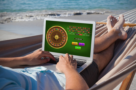 Online Roulette Game  against man using laptop while relaxing on hammock Banco de Imagens
