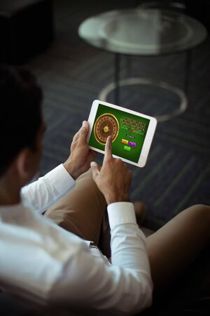 Online Roulette Game  against businessman using digital tablet at office