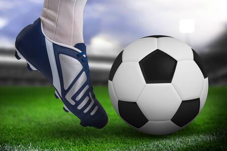Close up of football player kicking ball against close-up of soccer field Imagens