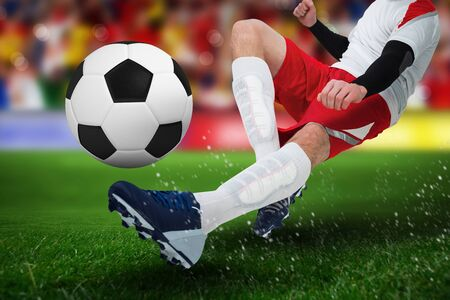 Football player in white kicking against soccer stadium Imagens