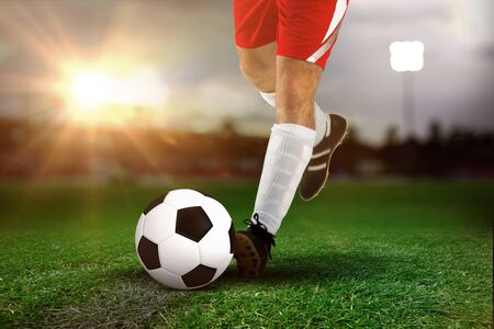 Football player in white kicking against close-up of soccer field Imagens