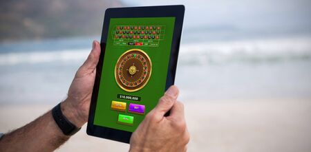 Online Roulette Game  against cropped image of man using tablet