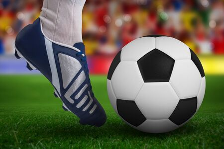Close up of football player kicking ball against soccer stadium