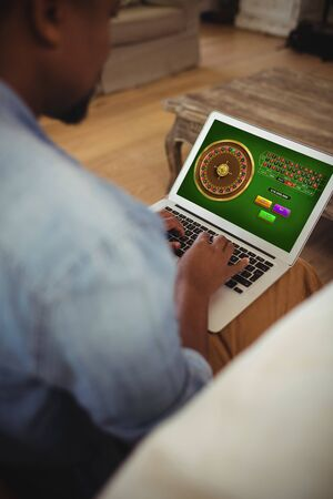 Online Roulette Game  against man using laptop in living room