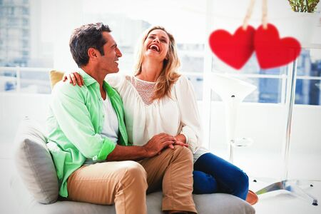 Hearts hanging on a line against couple relaxing on sofa at home