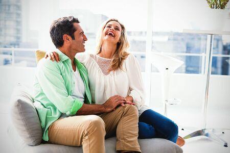 Happy couple relaxing on sofa at home 版權商用圖片