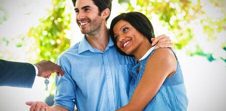 Agente de bienes raíces dando las llaves de la casa a la pareja en casa Foto de archivo