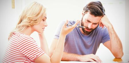 Worried young couple checking on bills at home 版權商用圖片