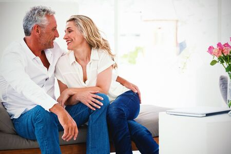 Romantic mature couple sitting face to face at home