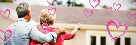 Red Hearts against senior couple looking at house while standing ih yard