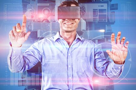 Smiling businessman using vr glasses against composite image of fitness interface Imagens