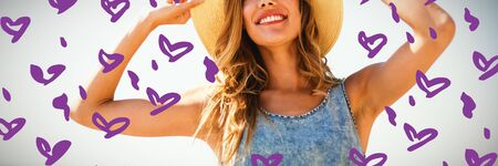 Heart shape purple paint on white background against smiling young woman standing against sky