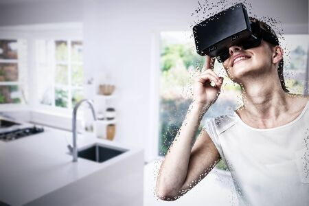 Low angle view of woman using virtual reality headset against empty modern kitchen 版權商用圖片