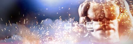 Mid section of muscular athlete exercising with dumbbell against firework bursting sparkle background
