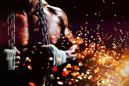 Midsection of muscular man holding chain against firework bursting sparkle background