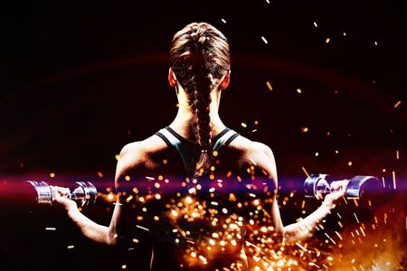 Rear view of braided hair woman lifting dumbbells against firework bursting sparkle background