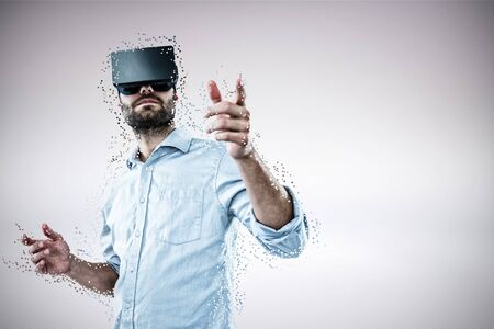 Low angle view of man using vr rift headset against grey background