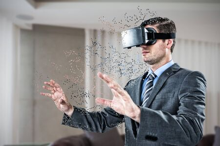 Businessman gesturing while using virtual reality headset against brown leather couch in a modern living room
