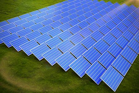 Blue solar panels against landscape with trees against sky Banco de Imagens