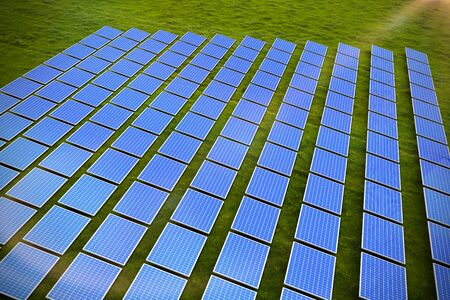 Solar panels  against landscape with trees against sky