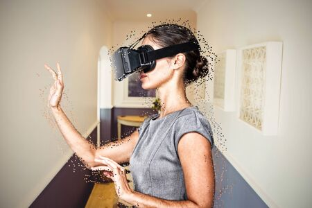 Side view of young woman gesturing while using virtual video glasses against view of house hallway 版權商用圖片