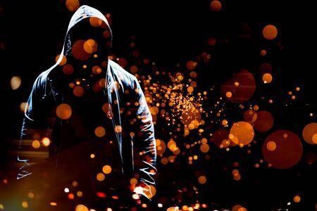 Portrait of confident man in hood against firework bursting sparkle background