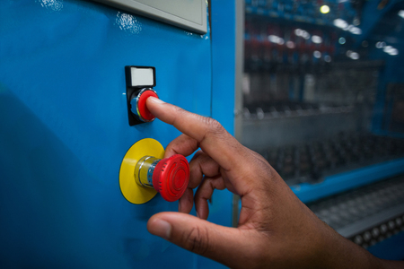 Hand pressing a red button in a electric room Imagens