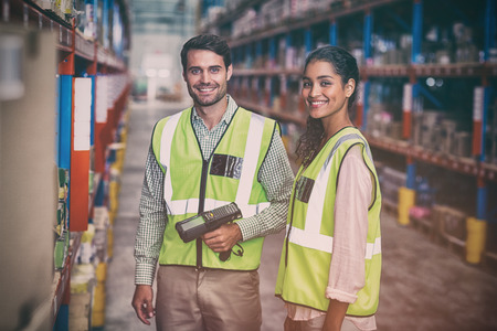 Portrait of smiling warehouse workers scanning box in warehouse Archivio Fotografico