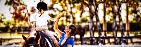 Side view of woman giving high five to girl sitting on horse in paddock Banco de Imagens
