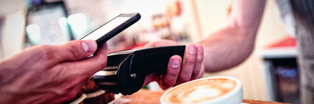 Close-up of customer with cellphone and male barista with card reader at counter in coffee shop