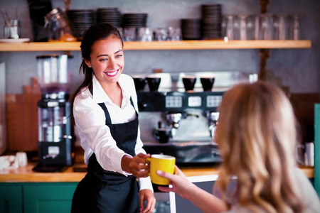 Waitress offering a cup of coffee in cafe 免版税图像