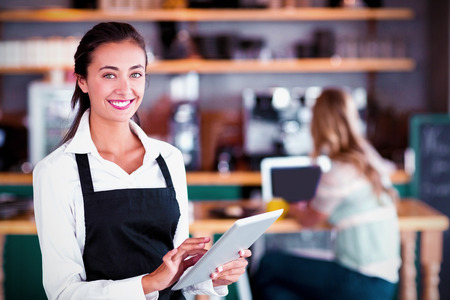 Portrait of smiling waitress using digital tablet in cafe